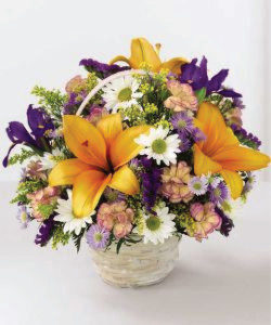Assorted flowers in a white wash or natural basket